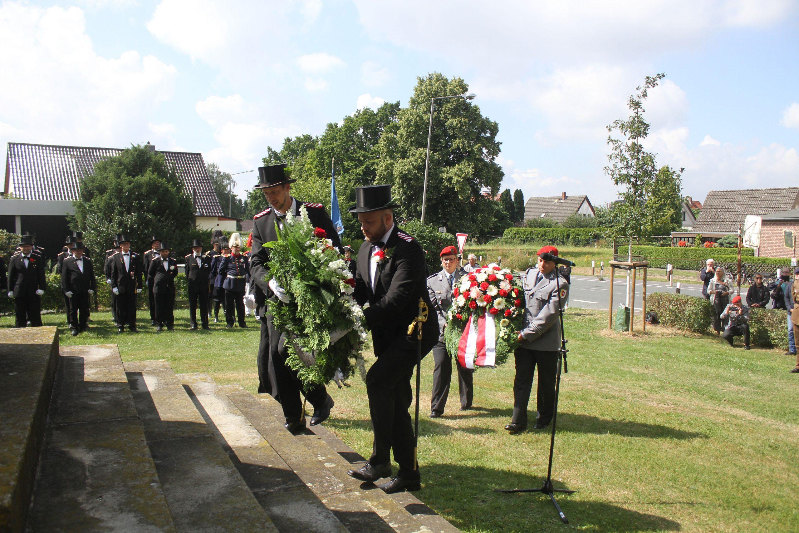 Mitglieder des Bürgerbataillons und der Mindener Pioniere legen Kränze am Denkmal in Todtenhausen ab.